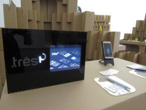 Exposição em uma mesa de uma tela em acrílico com tablet e um celular mostrando o projeto