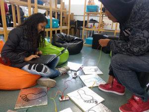 Dois alunos finalizando as configurações com chapas de alumínio, circuitos notebook