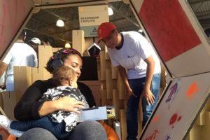 Visitante com seu bebê utilizam a cabine do projeto