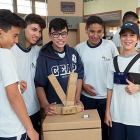 Cinco alunos mostram um protótipo de papelão